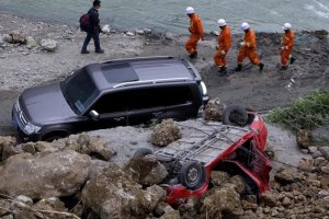 EFE - WUX39 BAOXIN (CHINA) 22/04/2013.- Un equipo de rescate pasa por delante de un coche destruido por el desprendimiento de tierras registrado tras el terremoto, en el condado de Baoxin (China) hoy,