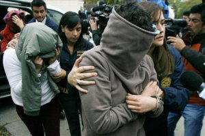 Los detenidos Natalia Guerra (c), Carla Franchy (i, atrás), y María del Pilar Alvarez (c), miembros de una secta que el pasado noviembre quemó vivo a un niño recién nacido, llegan a un tribunal para ser judicializados este jueves, en Qulipué (Chile). EFE