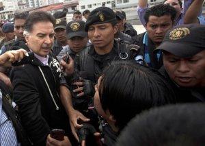 El ex presidente guatemalteco Alfonso Portillo, izquierda, habla con la prensa cuando la policía lo escolta a un avión que lo llevará a Estados Unidos desde Guatemala, viernes 24 de mayo de 2013. Portillo fue extraditado a Estados Unidos para responder a acusaciones de lavar 70 millones de dólares a través de cuentas bancarias estadounidenses. AP Foto