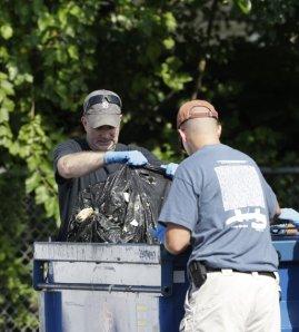 Investigadores sacan una bolsa de basura de un contenedor el domingo 21 de julio de 2013 cerca de donde encontraron hace poco tres cadáveres en East Cleveland, Ohio. Foto AP