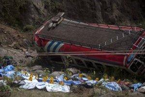 Piezas de plástico numeradas yacen sobre cadáveres de pasajeros que viajaban en un autobús que cayó a un profundo cañón en San Martin Jilotepeque, en el noroeste de Guatemala, el lunes 9 de septiembre de 2013. (Foto AP/