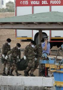 Soldados italianos llevan bolsas con cadáveres en la isla de Lampedusa, Italia, el domingo 6 de octubre del 2013, luego del hundimiento de un barco con inmigrantes africanos. Hasta ahora se han registrado 155 sobrevivientes y 111 cadáveres recuperados. (Foto AP