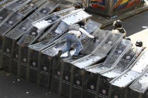 Un manifestante salta sobre una hilera de escudos policiales durante unas protestas en contra del Gobierno de Venezuela en Caracas, feb 12 2014. Las autoridades de Venezuela emitieron una orden de captura contra el líder de la oposición Leopoldo López, uno de los organizadores de las marchas antigubernamentales donde hubo enfrentamientos que dejaron el miércoles tres muertos y decenas de heridos. REUTERS