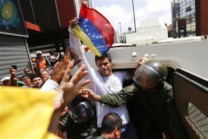 El líder de la oposición venezolana Leopoldo López (en el centro con la bandera) al momento de entrar a la tanqueta de la Guardia Nacional en Caracas, 18 de febrero del 2014. El dirigente, buscado bajo cargos de incitar a la violencia en las manifestaciones antigubernamentales que sacuden Venezuela, se entregó el martes a las fuerzas de seguridad ante miles de seguidores, mientras las protestas subían de temperatura. REUTERS
