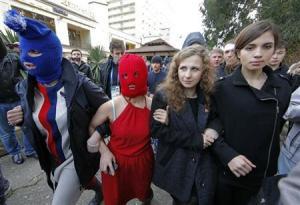 Integrantes del grupo activista Pussy Riot difundieron el jueves un nuevo vídeo musical criticando la celebración de los Juegos Olímpicos en Rusia y su trayectoria en derechos humanos, en un raro signo de disensión durante los Juegos. En la imagen los miembros de la banda rusa de punk Pussy Riot Maria Alyokhina (2da D) y Nadezhda Tolokonnikova (D) junto con miembros enmascaradas de la banda caminan tras hablar con los periodistas durante los Juegos de Sochi 2014 en Adler el 20 de febrero de 2014. REUTERS/