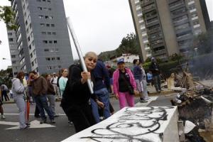 Una opostitora al Gobierno de Nicolás Maduro en Venezuela golpea piezas de antiguos muebles para fabricar barricadas en medio de una protesta en Caracas, feb 20 2014. Los enfrentamientos entre manifestantes y las fuerzas de seguridad recrudecieron el jueves en Venezuela, mientras opositores al presidente socialista Nicolás Maduro quemaban basura en improvisadas barricadas en Caracas y en otras ciudades del país. REUTERS
