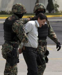 """Joaquín """"El Chapo"""" Guzmán es escoltado con las manos esposadas hacia un helicóptero por marinos de la Armada de México en el hangar de la Marina en el aeropuerto de la Ciudad de México, el sábado 22 de febrero de 2014. (Foto AP"""