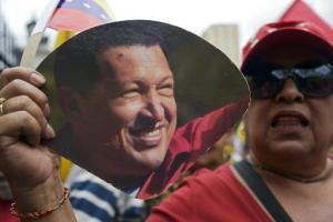 Una mujer muestra un retrato del fallecido Hugo Chávez durante una marcha a favor del gobierno de Nicolás Maduro, el 23 de febrero de 2014 en Caracas (AFP