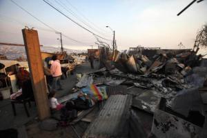 La gente intenta descansar junto a los escombros de lo que era su casa tras un incendio en la ciudad de Valparaíso, Chile, el domingo 13 de abril de 2014. Al menos 16 personas murieron la madrugada del domingo y 500 casas resultaron completamente destruidas en el mayor incendio de los últimos 60 años en ese puerto chileno. (AP foto