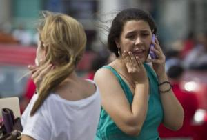 Una mujer habla por teléfono celular mientras abandona un edificio en Managua, Nicaragua, el viernes 11 de abril de 2014. Un segundo sismo de magnitud 6.6 sacudió a Nicaragua el viernes, que siguió a otro registrado el jueves. (AP Photo