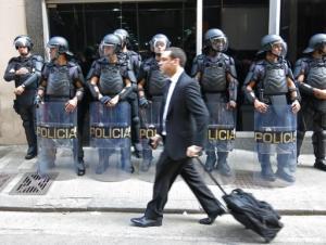 Un peatón camina frente a un grupo de policías que bloquean la entrada al Departamento de Transportación al que llegaron trabajadores del metro para negociar mejortes condiciones salariales en Sao Paulo, Brasil, el lunes 9 de junio de 2014. (Foto de AP