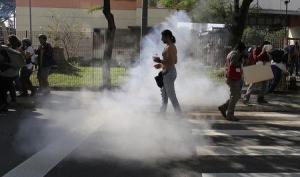La policía brasileña usó gas lacrimógeno para dispersar a un pequeño grupo de manifestantes contra el Mundial de fútbol el jueves en el este de Sao Paulo, mostró el canal local de televisión Globo News. En la imagen, una manifestante camina entre gas lacrimógeno disparado por la policía durante una protesta contra el Mundial en Sao Paulo, el 12 de junio de 2014. REUTERS/
