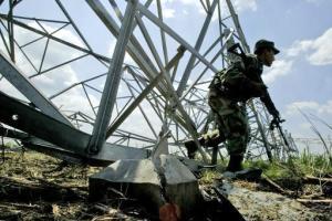 Un soldado colombiano vigila una torre de electricidad derrumbada por una explosión, el 8 de febrero de 2007 en El Placer, municipalidad de Palmira, departamento de Valle del Cauca (AFP/
