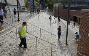 Varias personas caminan entre el foro Pauley Pavilion y un estacionamiento del campus de la Universidad de California en Los Ángeles después de una inundación causada por la ruptura de una tubería