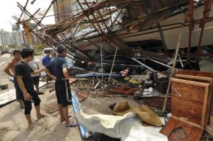 En esta imagen del sábado 29 de julio del 2014 dada a conocer por la agencia china de noticias Xinhua se observa un vehículo debajo de un edificio colapsado tras el paso del tifón Rammasun por Haikou, capital de la sureña provincia china de Hainan. (Foto AP