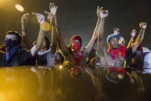 En la imagen, manifestantes hacen gestos desafiando un toque de queda instaurado para calmar las protestas tras la muerte de un adolescente de raza negra en Ferguson, Misuri. 17 de agosto, 2014. El fiscal general de Estados Unidos, Eric Holder, ordenó el domingo una autopsia federal al cuerpo de un joven que falleció baleado por un oficial de policía en Ferguson, Misuri, a fin de garantizar a la familia y la comunidad que se investigará a fondo una muerte que ha desatado días de protestas raciales. REUTERS