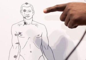 El adolescente negro Michael Brown, que iba desarmado, murió tras recibir al menos seis balazos de un policía blanco, dijo el lunes el abogado de la familia del joven, sobre un incidente que desató una semana de protestas y saqueos en la ciudad de Ferguson, en Estados Unidos. En la imagen, el abogado de la familia Brown muestra imágenes de las balas que impactaron en el cuerpo del joven Michael Brown, en rueda de prensa el 18 de agosto en Ferguson. REUTERS/