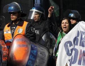 Una manifestante grita frases en contra del Gobierno cerca de policías antimotines, durante una protesta de trabajadores estatales que intentaban bloquear una calle en Buenos Aires, 27 de agosto del 2014. Sindicatos opositores y agrupaciones de izquierda protagonizaban el jueves la segunda huelga general del año contra el Gobierno de la presidenta argentina Cristina Fernández para reclamar mejoras salariales, en momentos de recesión económica y alta inflación. REUTERS/