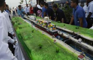 Trabajadores del Canal de Panamá llevan un gran pastel con la forma de la esclusa de Miraflores durante los festejos por el centenario del Canal Interoceánico en la ciudad de Panamá, viernes 15 de agosto de 2015. (AP Foto