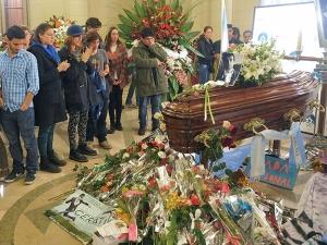 Personas se reúnen frente al féretro de Gustavo Ceratti, donde también se han colocado obsequios de admiradores del fallecido cantante