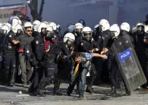 Policías antimotines turcos detienen a manifestantes al tiempo que usa gases lacrimógenos para dispersar gente que protestaba contra las políticas de Turquía en Siria, mientras se intensificaban los combates entre curdos sirios y extremistas del grupo Estado Islámico en Kobani, Siria, en Ankara, Turquía, el martes 7 de octubre de 2014. (Foto AP