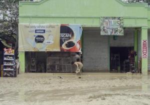 Un residente trata de sacar lodo de la entrada de su negocio en el pueblo de Alcantara, en la provincia de Cebu, en el centro de Filipinas, el martes, 30 de diciembre del 2014. (Foto AP/