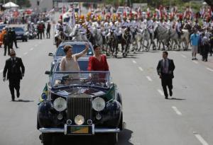 La presidenta de Brasil, Dilma Rousseff (izquierda), saluda a la multitud acompañada de su hija, Paula Rousseff Araujo, en un Rolls Royce hacia el Congreso Nacional para la ceremonia en la que prestará juramento para un segundo mandado de cuatro años, el jueves 1 de enero de 2015, en Brasilia. (Foto AP/